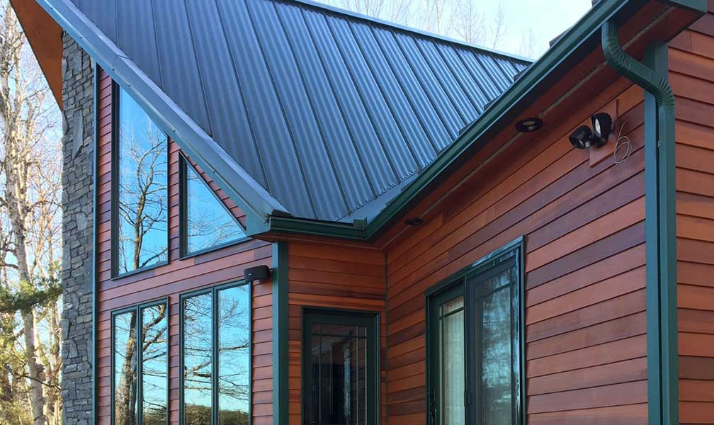 Earthadelic offers new gutter installations in a variety of colors to match any style. These green gutters on a log cabin provide a rustic look.