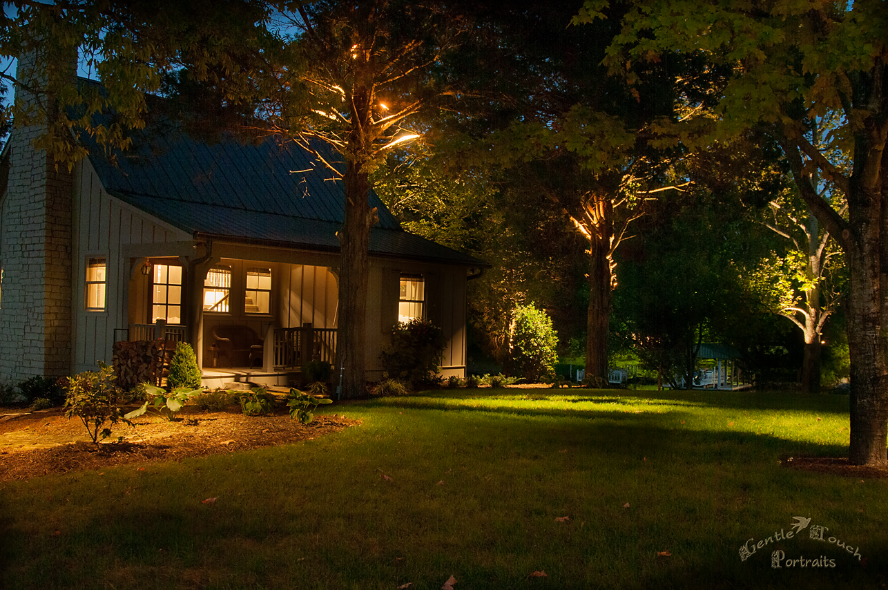Professional landscape lighting showcases this nestled cottage among the trees.